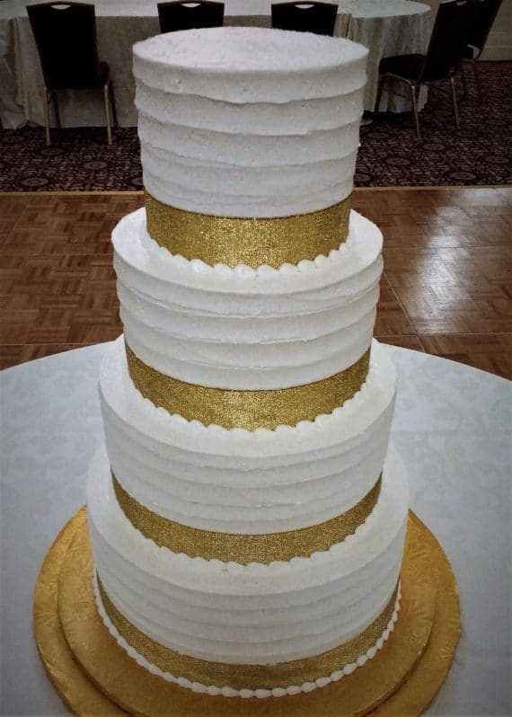 four tiered white and gold cake