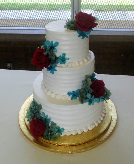 three tier flower cake with white frosting