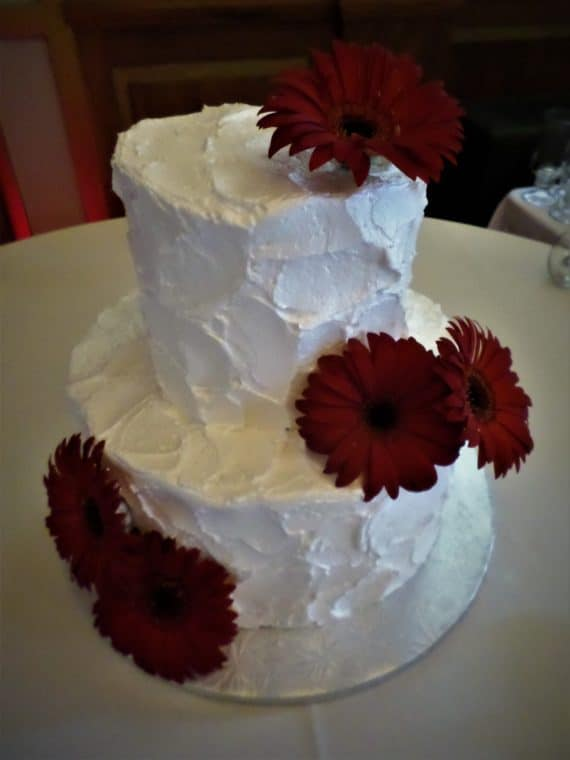 white tiered cake with red flowers